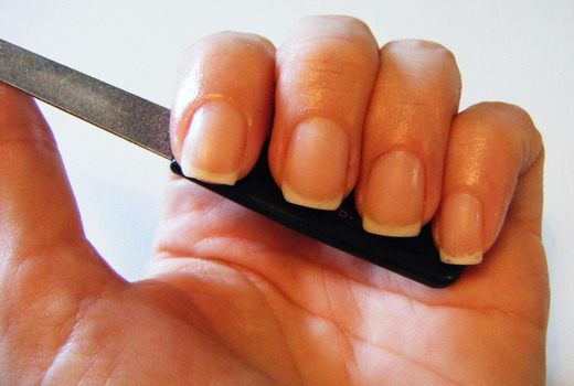 Рука с пилочкой для ногтей
